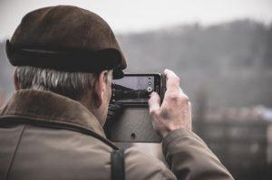 Senhor em um residencial para idosos tirando foto com um smartphone