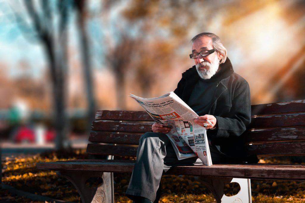 Senhor sentado no parque lendo matéria sobre lares para idosos