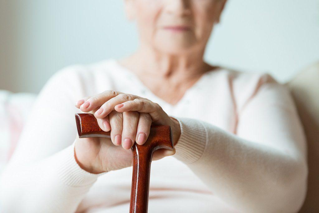 Mulher idosa sofrendo com dores da artrose sentada com o apoio de uma bengala