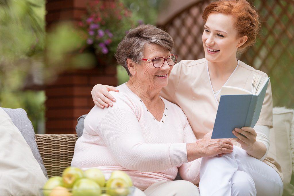Idosa lendo com um cuidador de idosos profissional em um banco no jardim