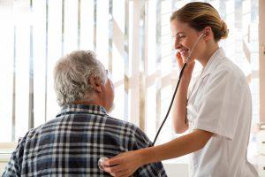 médica geriatra examinando paciente idoso com estetoscópio | Morada Primavera