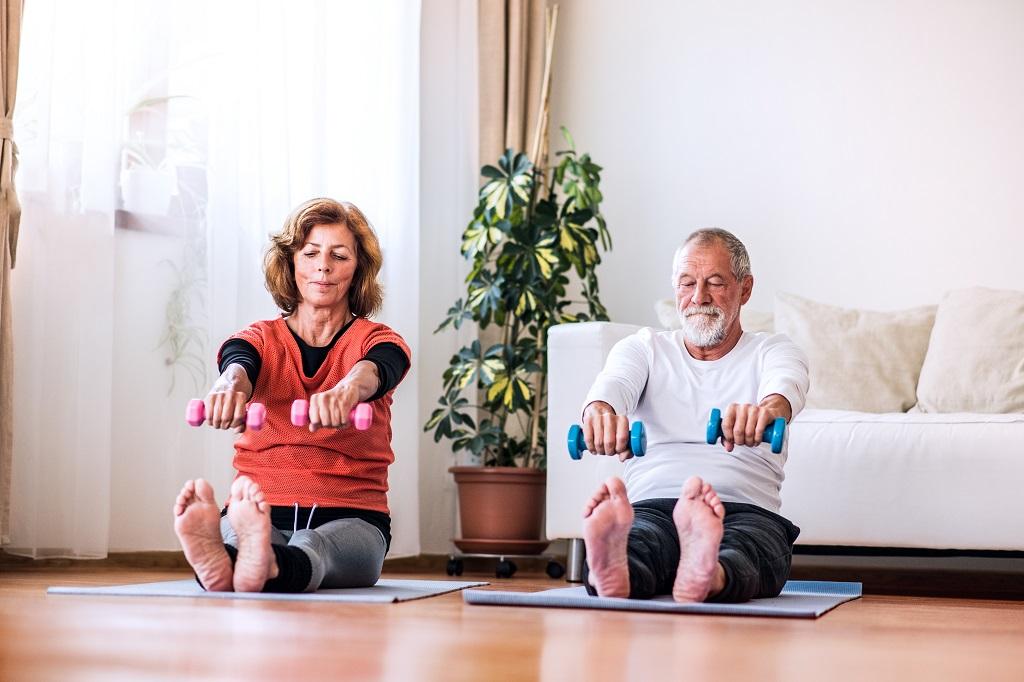 casal de idosos praticando exercícios dentro de casa