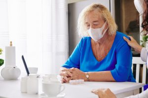 mulher idosa se protegendo do coronavírus usando máscara