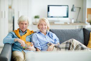 casal sentado no sofá assistindo filmes para idosos