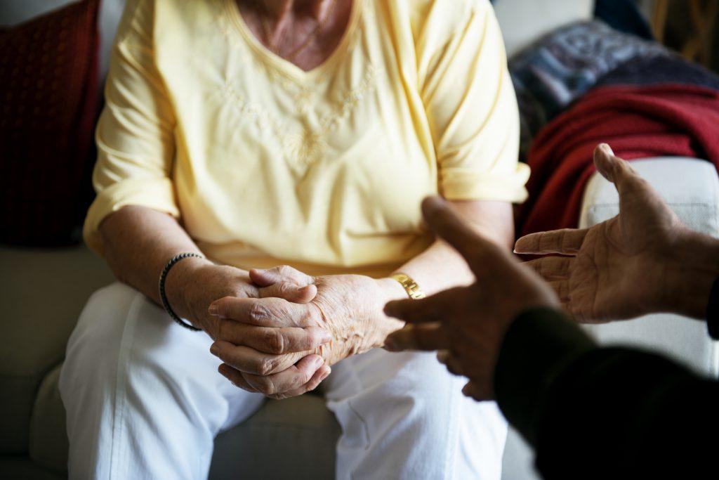 mãe idosa e filho sentados conversando sobre o isolamento social