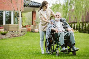 cuidadora passeando com idoso no jardim da casa de repouso